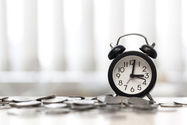 Reloj y monedas en la ventana del área de la mesa del escritorio, el tiempo es dinero