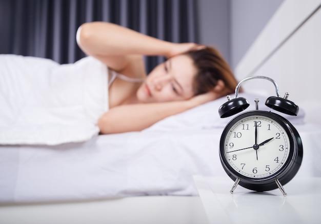 Reloj con mujer sin dormir en la cama
