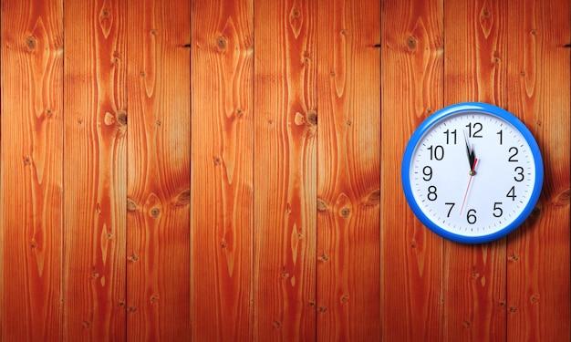 Reloj de pared azul con hora de medianoche sobre superficie de madera