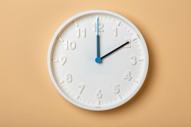 Reloj de pared blanco con segundero azul que muestra las dos en punto