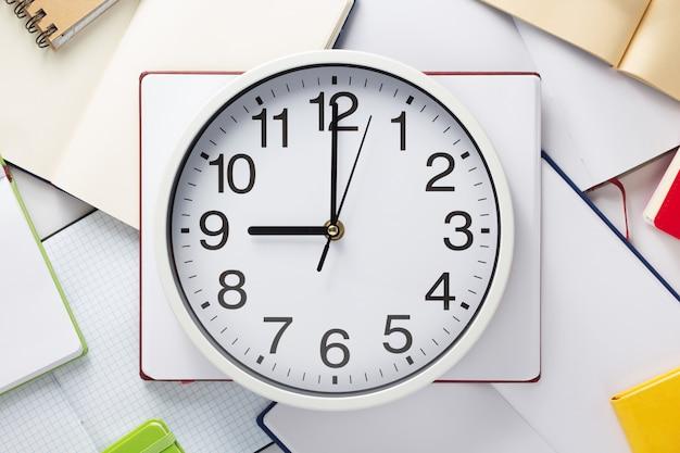 Reloj de pared y cuaderno abierto o libro