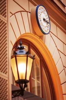 Reloj de pared y farola al atardecer. farolas iluminadas al atardecer. lámparas decorativas. lámpara mágica con una cálida luz amarilla en el crepúsculo de la ciudad.