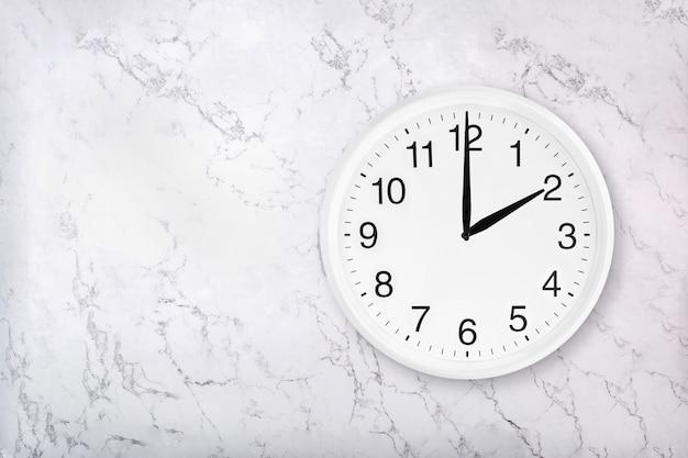Reloj de pared redondo blanco sobre fondo de mármol blanco natural. dos en punto.
