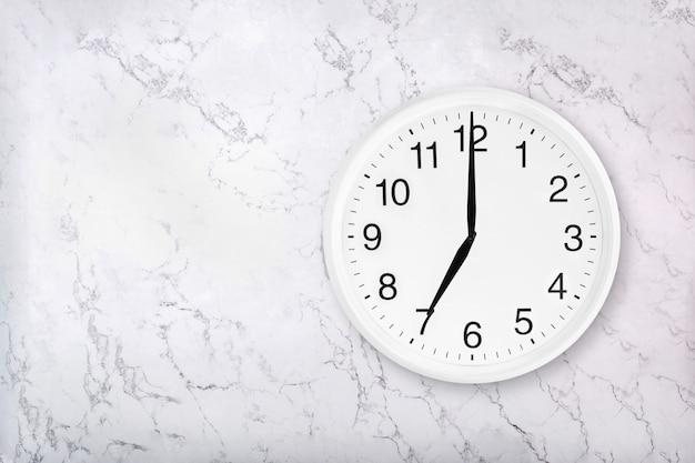 Reloj de pared redondo blanco sobre fondo de mármol blanco natural