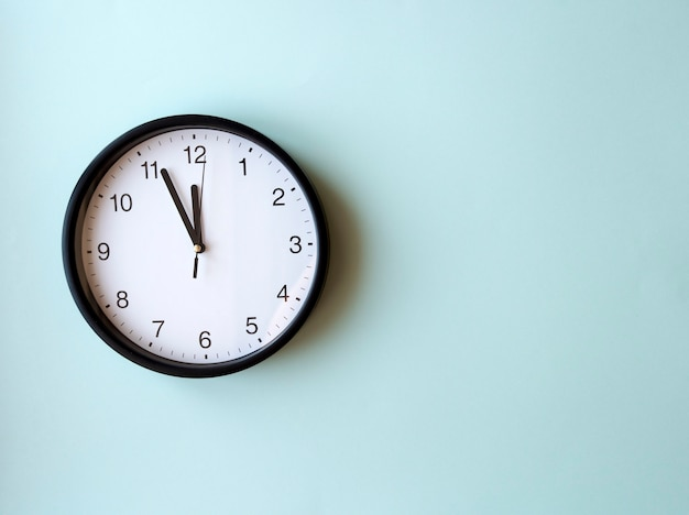 Reloj de pared redondo sobre superficie azul que muestra las 12 en punto, diseño, vista superior, lugar para el texto