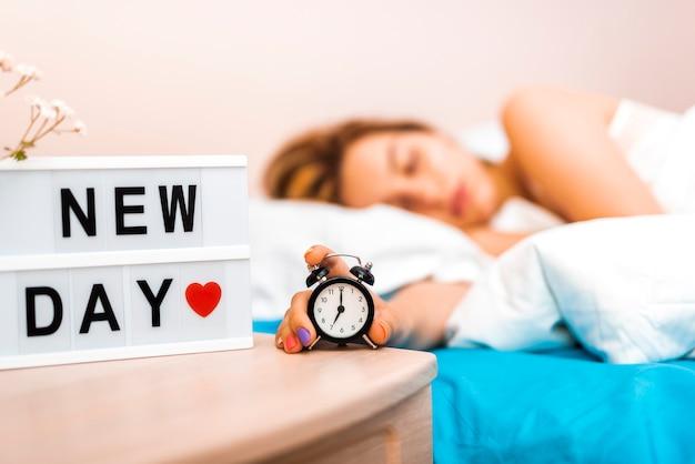 Reloj de primer plano sostenido por una mujer soñolienta