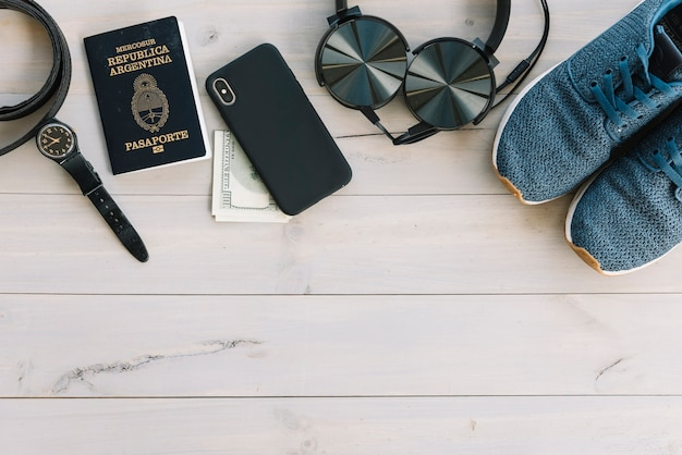 Reloj de pulsera; teléfono móvil; moneda; auriculares y zapatos en mesa de madera