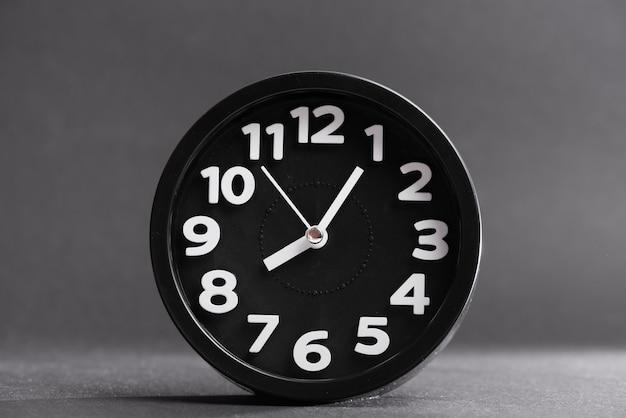 Reloj redondo negro sobre fondo gris.