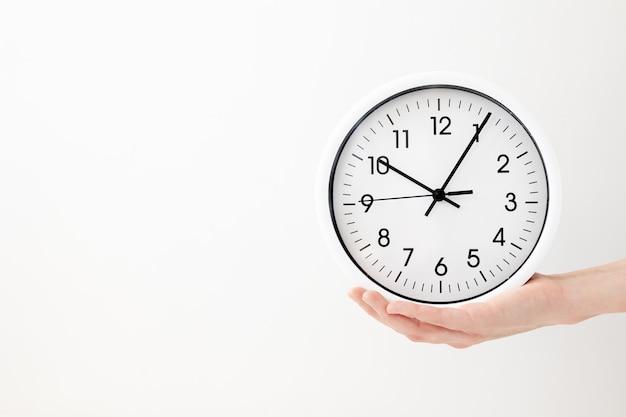 Reloj, reloj de flecha blanca sobre fondo blanco mano de mujer sosteniendo un reloj redondo con flechas negras, control, cronometraje, gestión del tiempo, tiempo, ven, tarde, perdiendo minutos, segundo