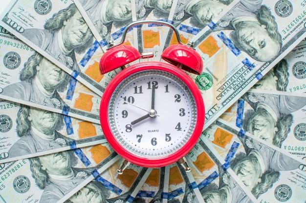 Reloj rojo en el fondo de dólares de dinero