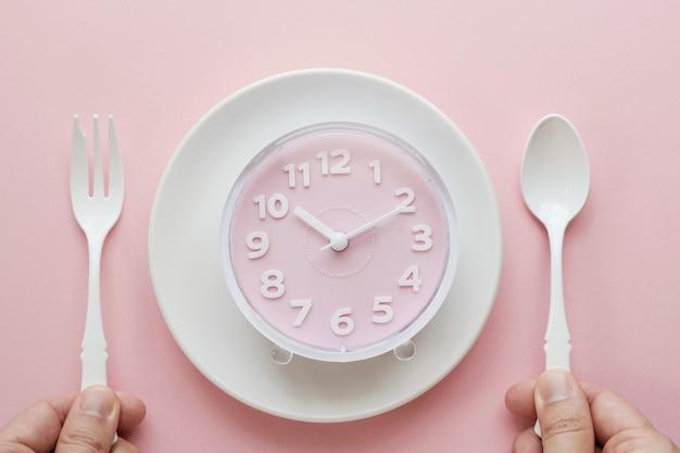Reloj rosa en plato blanco y manos sosteniendo cuchara y tenedor