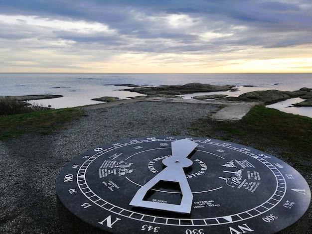 Reloj de sol rodeado por el mar durante la puesta de sol en rakke en noruega
