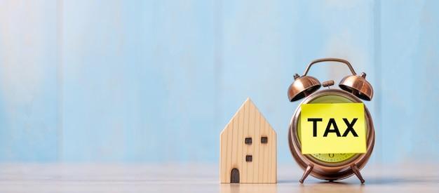 Reloj con texto de impuestos y modelo de casa en madera