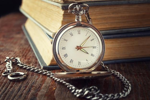 Reloj vintage en una cadena sobre un fondo de libros antiguos