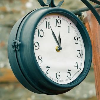 Reloj vintage de la calle. 5 minutos para las doce concepto