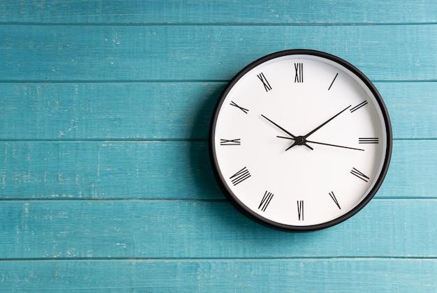 Reloj vintage con números romanos sobre fondo de madera.