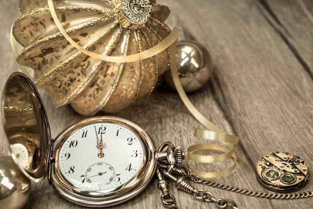 Reloj vintage que muestra de cinco a doce y decoraciones en madera.