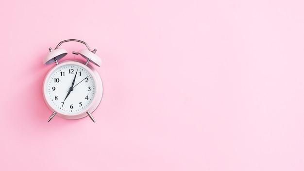 Reloj vintage de vista superior con fondo rosa