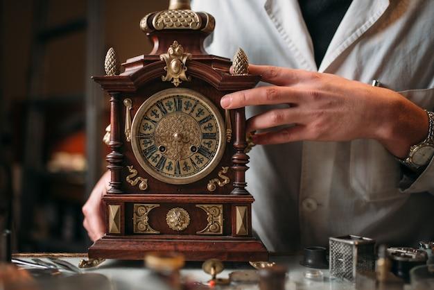 Relojero con antiguo reloj de escritorio mecánico