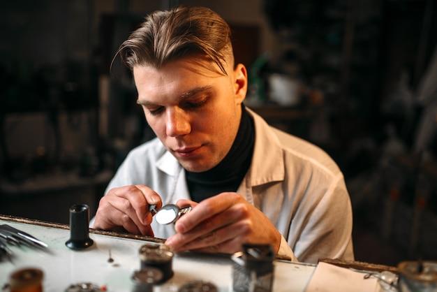 Relojero reparar un reloj roto con pinzas