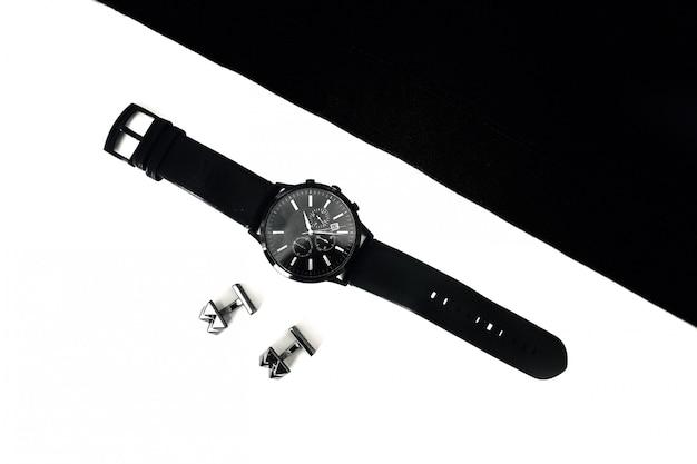 Relojes y gemelos en la mesa, blanco y negro.