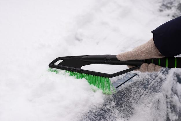 Remoción de nieve, coche en nieve. la mujer limpia el coche de la nieve.