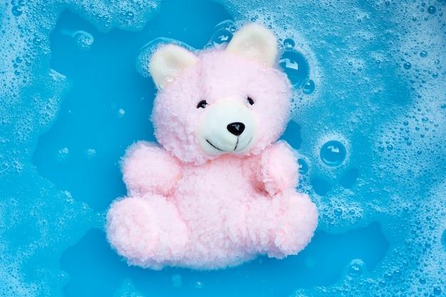 Remojar el oso de juguete en detergente para ropa, disolución de agua