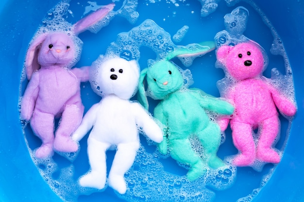 Remoje la muñeca de conejo con el osito de peluche en detergente para ropa, disuelva el agua antes de lavar. concepto de lavandería,