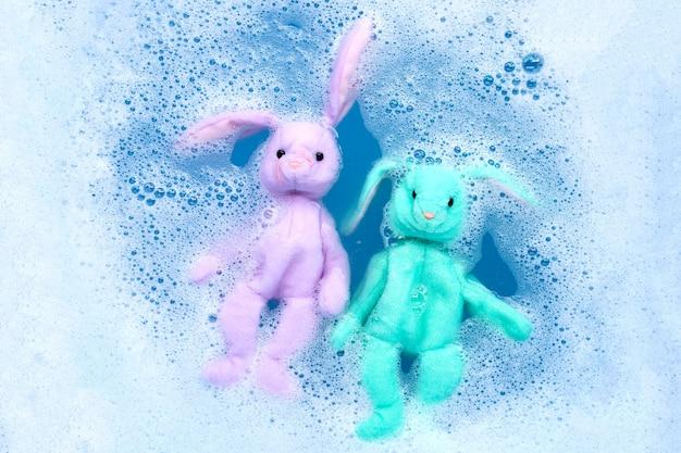 Remoje las muñecas de conejo en agua detergente para lavar antes de lavarlas. concepto de lavandería