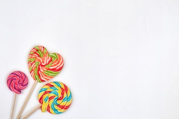 Remolino de caramelo de piruleta de arco iris sobre superficie blanca