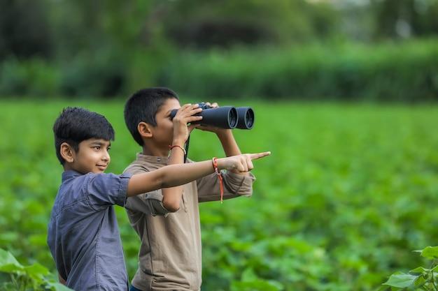 Remolque niño indio disfruta en la naturaleza con binoculares