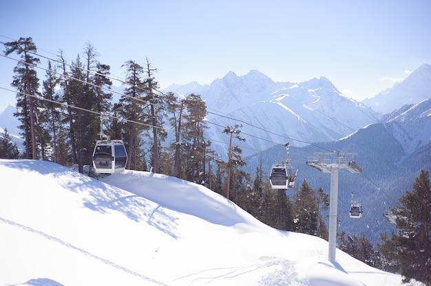 Remonte con asientos que recorren la montaña y senderos de cielos y tablas de snowboard.