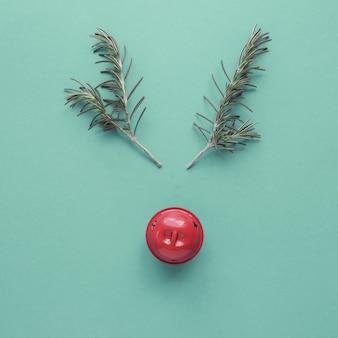 Reno mínimo hecho de romero y campana de decoración roja, fondo festivo de navidad hipster