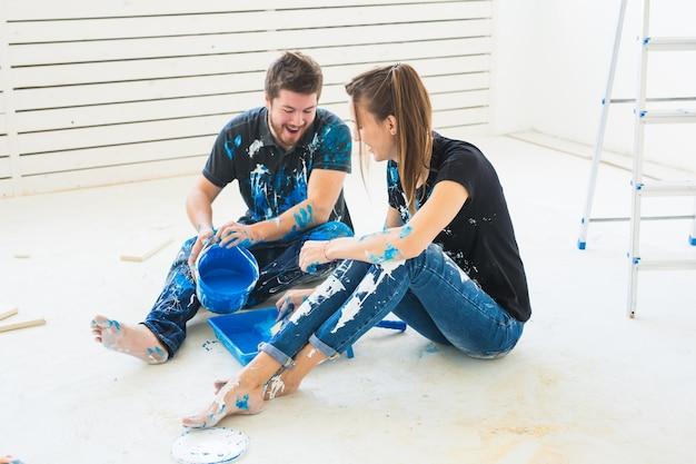 Renovación, redecoración y concepto de familia - pareja joven vierte pintura.