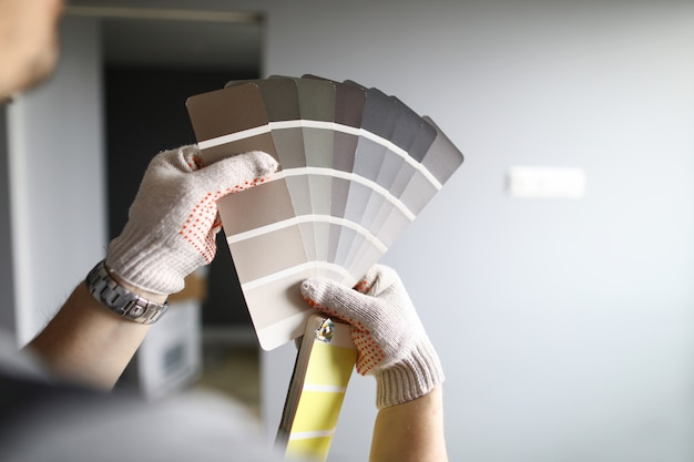 Repairmans manos en guantes con paleta de colores sobre paredes grises renovadas en piso. reparador profesional durante el concepto de trabajo.