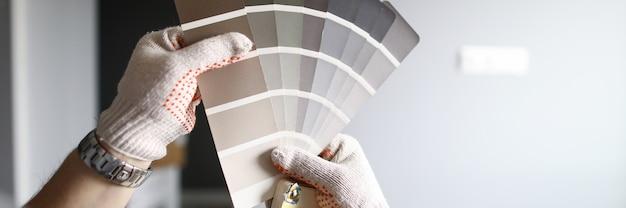 Repairmans manos con paleta de colores sobre paredes grises renovadas