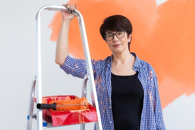 Reparación en el apartamento. feliz mujer de mediana edad pinta la pared con pintura.