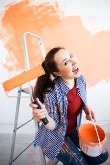 Reparación en el apartamento. mujer divertida pinta la pared con pintura.