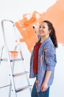 Reparación en el apartamento. mujer feliz pinta la pared con pintura.