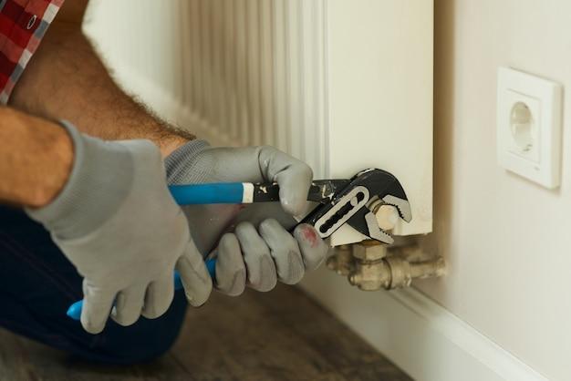 Reparación de calefacción primer plano de manos masculinas con llave ajustable manitas repara una calefacción