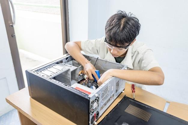 Reparación de computadoras de personas con soldador en concepto de centro de servicio