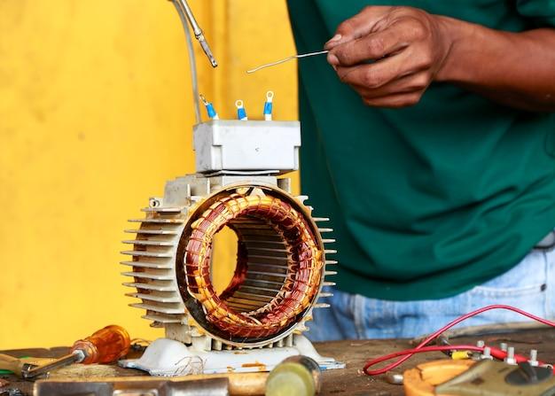 Reparación desmontar el motor eléctrico viejo muestra la bobina de cableado durante el cambio de cojinete