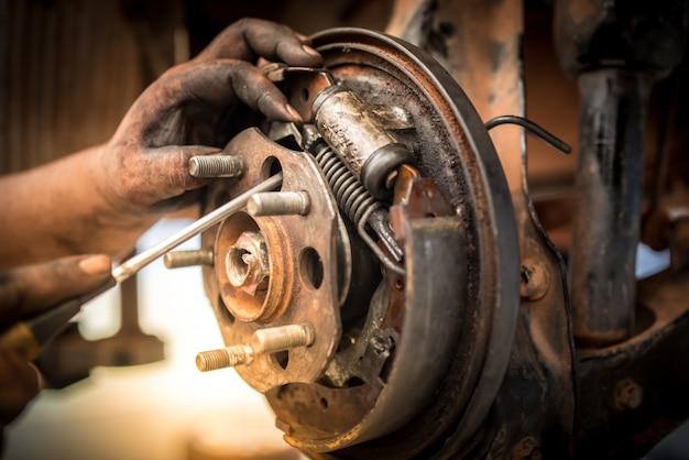 Reparación de frenos o inspecciones de sistemas de frenos y el reemplazo de nuevas pastillas de freno en manos de mecánicos que cambian las pastillas de freno de los talleres de reparación de automóviles.