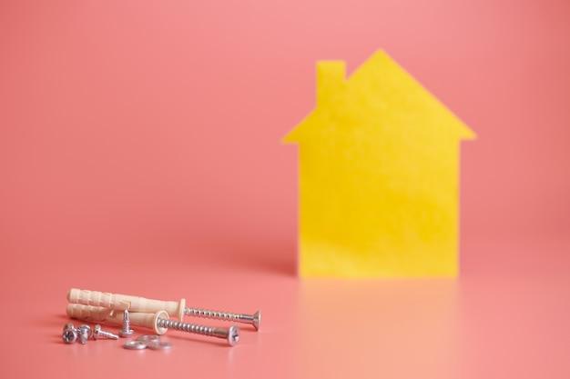 Reparación del hogar y concepto redecorado. renovación de la casa. tornillos y casa amarilla