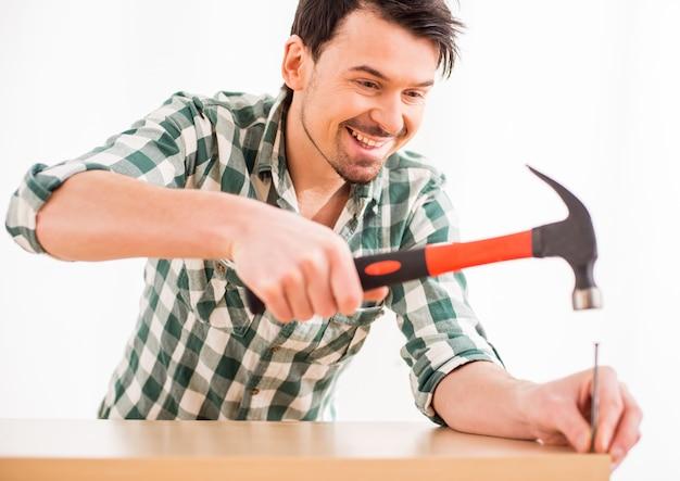 Reparación joven martillo un clavo en casa.