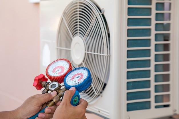 Reparación mecánica de aire usando un medidor múltiple para llenar el aire acondicionado doméstico