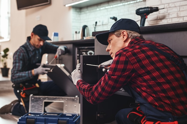 Reparación rápida y de calidad técnico de dos hombres sentado cerca del lavavajillas