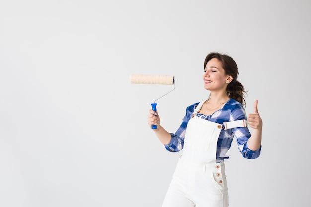 Reparación, renovación, nuevo hogar y concepto de personas - mujer joven haciendo redecoración y muéstranos los pulgares