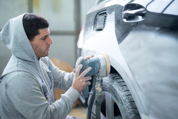 Reparador de automóviles pulido de la carrocería con una máquina que prepara el vehículo para pintar