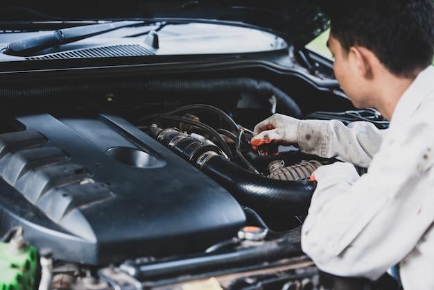 Reparador de automóviles con un uniforme blanco de pie y sosteniendo una llave que es una herramienta esencial para un mecánico